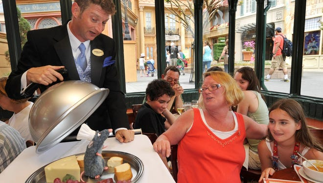 """Epcot guest Kathleen Kramer (left), and her daughter Rebecca, enjoy a visit from """"Chef Remy"""" and French Maitre d' """"Armand"""" at Les Chefs de France restaurant in Epcot in Lake Buena Vista, Fla."""
