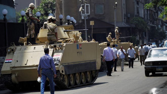 Egyptian military soldiers stand guard atop armored personnel carriers at Maspero, an Egypt's state TV and radio station, not far from Tahrir Square in Cairo on Saturday.