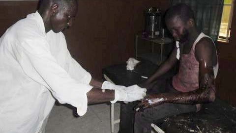 This mobile phone photo shows a doctor attends to a student from Government Secondary School in Mamudo, at the Potiskum General Hospital in Nigeria, following an attack July 6, 2013, by Islamic militants.