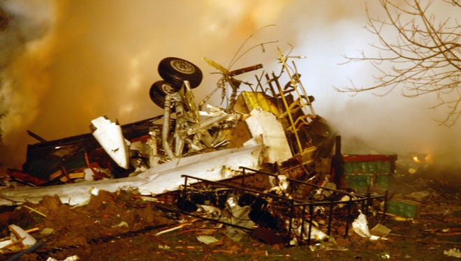 The wreckage of Colgan Air Flight 3407 lies amid smoke after crashing into a suburban Buffalo home and erupting into flames late Feb. 12, 2009.
