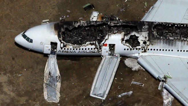 A Boeing 777 airplane lies burned on the runway after it crash landed at San Francisco International Airport. The Asiana Airlines passenger aircraft originated in Seoul, South Korea.