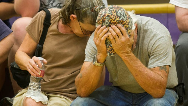 Gail Miller comforts her brother, Walt Adams, before a community meeting for Yarnell Hills Fire evacuees at the Red Cross Shelter in Wickenburg, Ariz., on July 6, 2013.