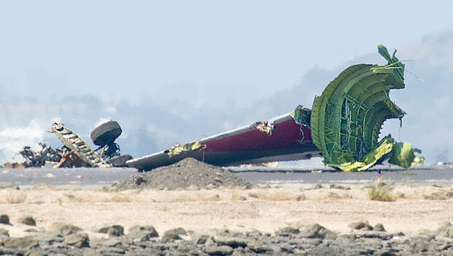 The detached tail and landing gear of Asiana Flight 214 rest on the tarmac after the plane crashed at San Francisco International Airport on Saturday.