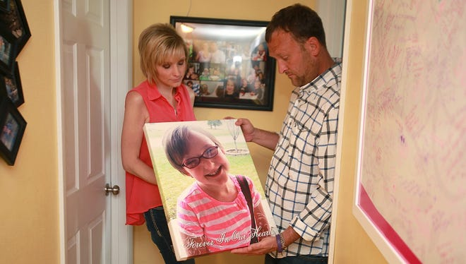 Heather and Drew Collins bring out a photo of their daughter, Elizabeth, from the bedroom of their Evansdale, Iowa, home, on Tuesday, July 2, 2013. This week will mark the first anniversary of the disappearance of Collins and her cousin, Lyric Cook-Morrissey.