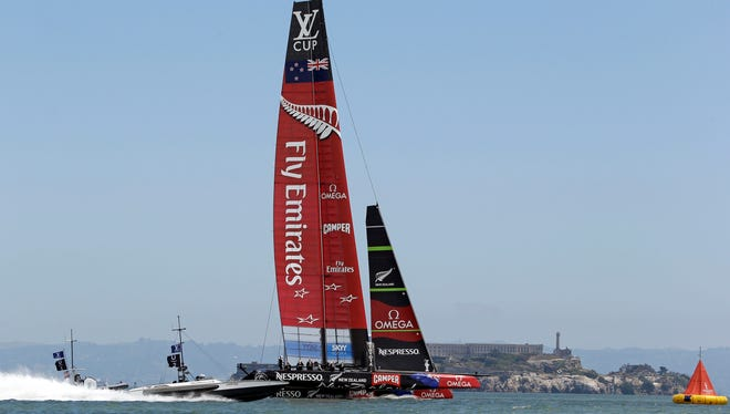 Emirates Team New Zealand races alone with Alcatraz Island in the background during an America's Cup challenger series sailing race Sunday in San Francisco.