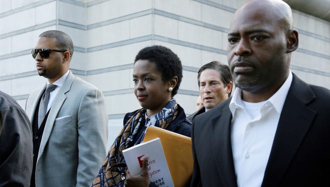 Eight-time Grammy Award-winning singer Lauryn Hill, center, leaves federal court in Newark after sentencing in her tax evasion case.