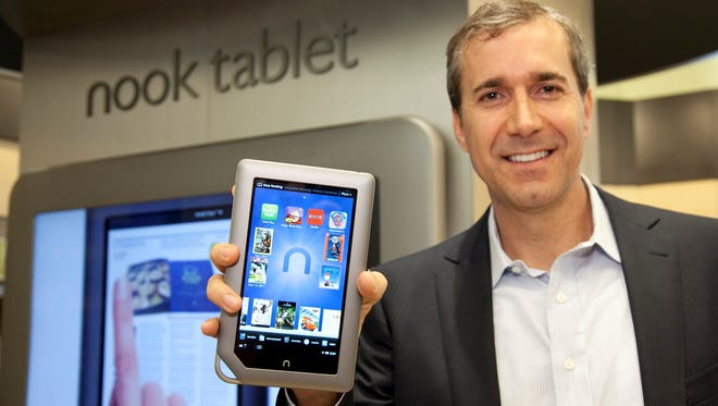Barnes , Noble CEO William Lynch holds the  NOOK Tablet. Lynch is resigning as chief executive after three years on the job.