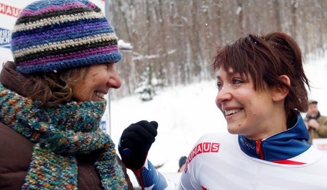 In a file photo from Feb. 24, 2012,  Katie Uhlaender, right, reacts with her mother Karen after winning the women's skeleton world championships in Lake Placid, N.Y.