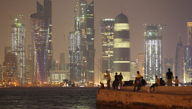 In a file photo from October 2011,  people fish along the waterfront along the Persian Gulf across from new, illuminated financial district skyscrapers at dusk in Doha, Qatar. Qatar will host the 2022 FIFA World Cup.