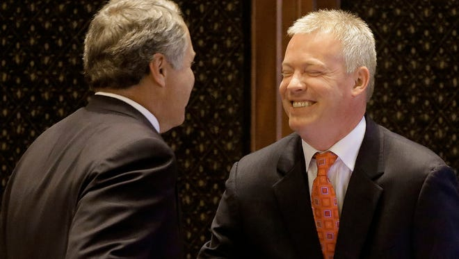 Illinois Rep. Brandon Phelps, D-Harrisburg, right, is congratulated by Illinois Rep. Jay Hoffman, D-Belleville, left, while on the House floor during session at the Illinois State Capitol on July 9.