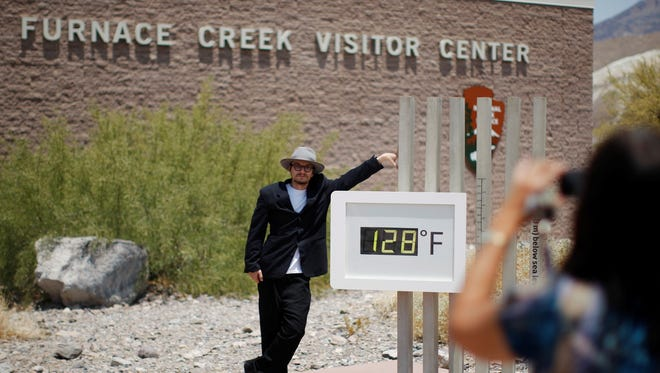 Kevin Martin of Corona, Calif., poses for a snapshot by an unofficial thermometer reading at Furnace Creek Visitor Center on June 30 in Death Valley.