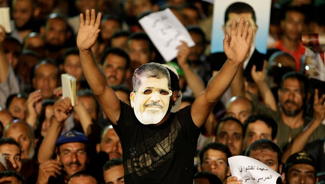 A supporter of ousted Egypt's President Mohammed Morsi, wears a mask that shows the face of Morsi during a demonstration after the Iftar prayer, evening meal when Muslims break their fast during the Islamic month of Ramadan, in Nasr City, Cairo, Egypt, on July 10.