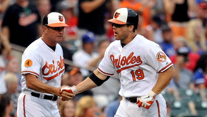Chris Davis (19) shakes hands with third base coach Bobby Dickerson after his 34th home run of the year.