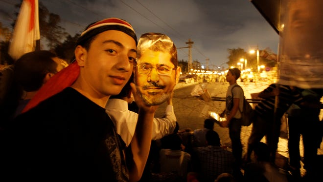 A supporter of Egypt's ousted President Mohammed Morsi poses with a paper mask of Morsi as he and others face Egyptian military soldiers near the presidential palace in Cairo, Egypt, on Saturday.