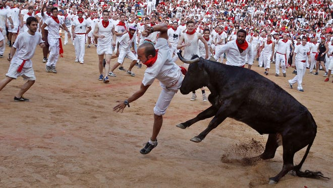 A reveler is pushed by a Torrestrella ranch bull.