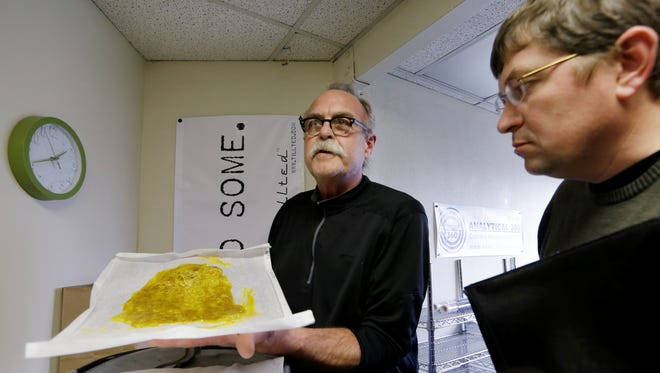 In this photo taken on April 4, Jim Andersen, left, displays butane hash oil to Mike Steenhout, comptroller of Washington's Liquor Control Board, at a marijuana growing facility in Seattle. Andersen has a 40-year history with hashish, the concentrated cannabis sometimes referred to as the cognac of the marijuana world. When Washington was on the verge of legalizing the sale of taxed pot last fall, Andersen decided to move back to his home state and turn his hobby into a full-time, legitimate paycheck-- a business that would supply state-licensed, recreational marijuana stores with high-quality hash oil.