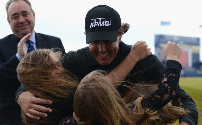 Phil Mickelson embraces his children Evan, Amanda (L) and Sophia after his victory in the Scottish Open.