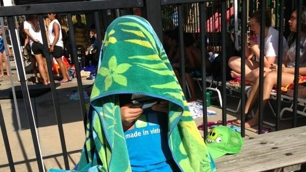 A 6-year-old boy hides from the sun while playing video game in Herndon, Va.