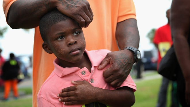 Seven-year-old Terrance Smith II stands with his father during a protest against the George Zimmerman verdict Sunday in Sanford, Fla.