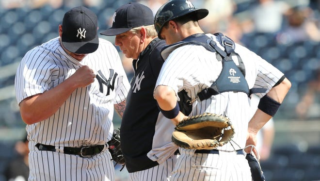New York Yankees pitching coach Larry Rothschild, middle, talks to relief pitcher Joba Chamberlain, left, in the ninth inning Sunday. The Yankees fell to the Minnesota Twins 10-4.
