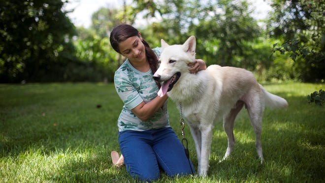 Elizabeth Arroyo and her dog, Raiden, on Thursday, July 11, 2013, at their home in Greenwood, Ind. Arroyo found an ad on Craigslist attempting to sell Raiden after he wandered from Arroyo's home.