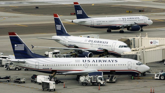 US Airways planes occupy gates and taxi for takeoff at Sky Harbor Airport in Phoenix.