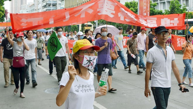 Protesters who oppose the uranium processing plan in Heshan, parade through a street in Jiangmen, China on July 12. Local authorities scrapped a plan to build a uranium-processing plant a day later.