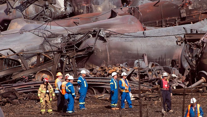 Workers stand before mangled tanker cars Tuesday, July 16, 2013, at the crash site of the train derailment and fire in Lac-Megantic, Quebec.  The July 6, 2013, accident  left 37 people confirmed dead and another 13 missing and presumed dead.  (AP Photo/Ryan Remiorz, pool) ORG XMIT: RYR104