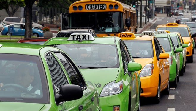 Los Angeles area taxi drivers circle City Hall last month to protest unregulated ride-share services being promoted through smartphone apps.