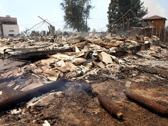 What remains of a home continues to smoke Pine Springs Ranch, Calif., after the Mountain Fire destroyed it July 16, 2013.