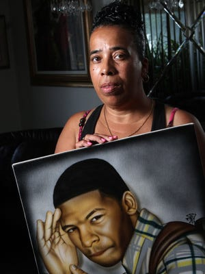 071713- Teen Suicide Case -Linda Rogers holds a portrait of her grandson, Roger 'Mac' Ellerbe Jr., who committed suicide in 2009, seen Wednesday, July 17, 2013 at her Newark area home. The News Journal/William Bretzger