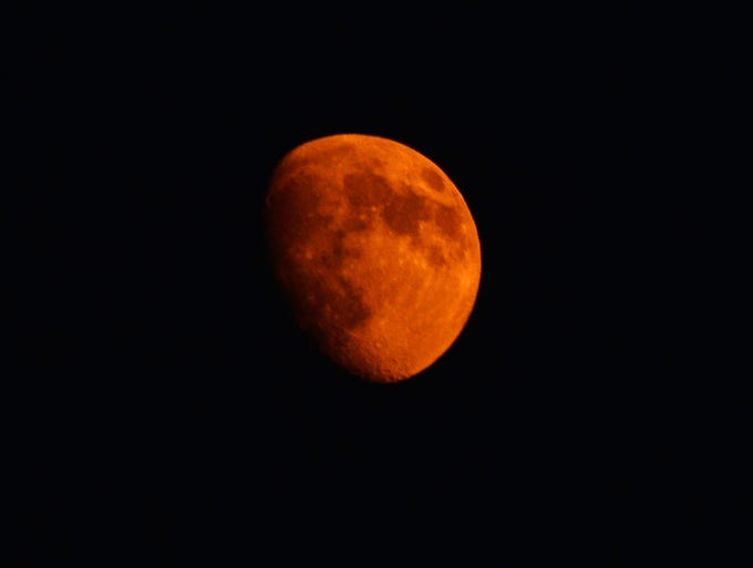 The moon turns an orange color from the smoke of the Mountain Fire July 18 near Idyllwild, California.