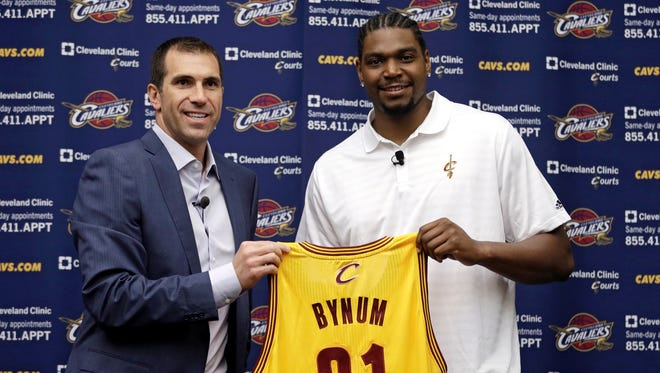 Andrew Bynum joins Cavaliers GM Chris Grant in holding up his new jersey.