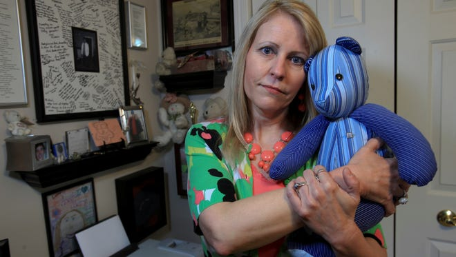 Missy Gousha cuddles a teddy bear that was made from her son Michael's favorite shirt after his suicide at age 23.  She is standing next to memorial items she has on display in her home.