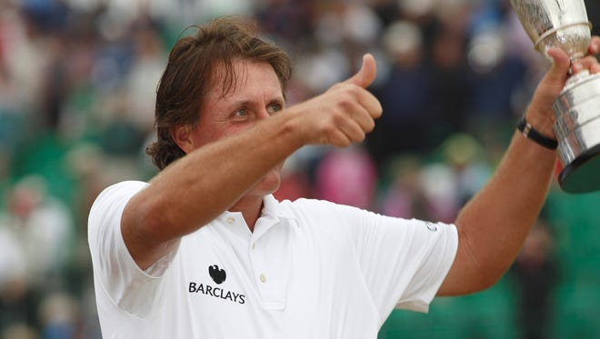 Phil Mickelson celebrates winning the 2013 The Open Championship trophy at Muirfield Golf Club.
