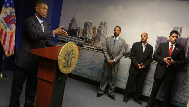Detroit Emergency Financial Manager Kevyn Orr, left, announces that he filed for municipal bankruptcy during a news conference at the Coleman A. Young municipal building in Detroit on July 18, 2013.