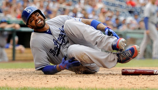 Dodgers' fielder Matt Kemp grimaces as he was out at home and hurt on the play.