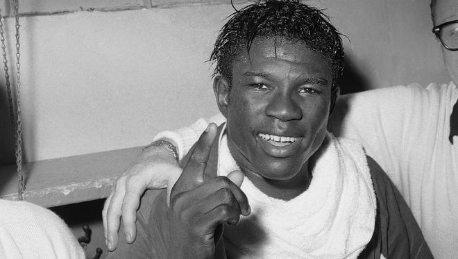 In this June 8, 1963 file photo, Emile Griffith smiles in the dressing room after regaining his welterweight world championship title by defeating Luis Rodriguez, at New York.
