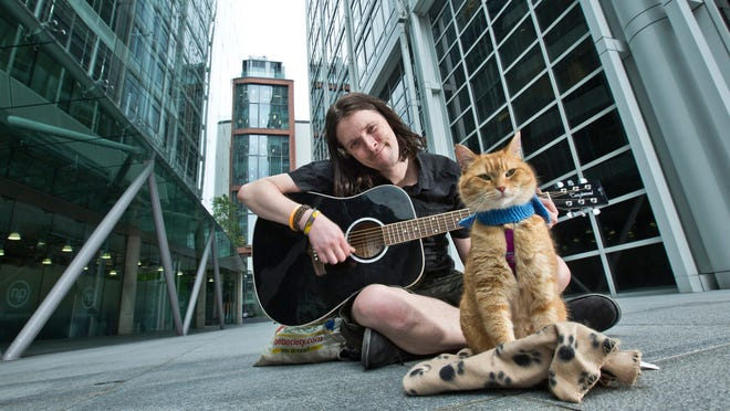James Bowen and his cat, Bob, near Covent Garden in London, where Bowen, homeless and addicted to heroin, used to play guitar for money.