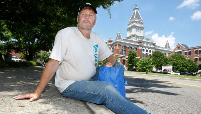 The Rev. Willie Lyle rests along a curb in downtown Clarksville, Tenn. The Sango United Methodist Church pastor went undercover, living on the streets for a week in June.