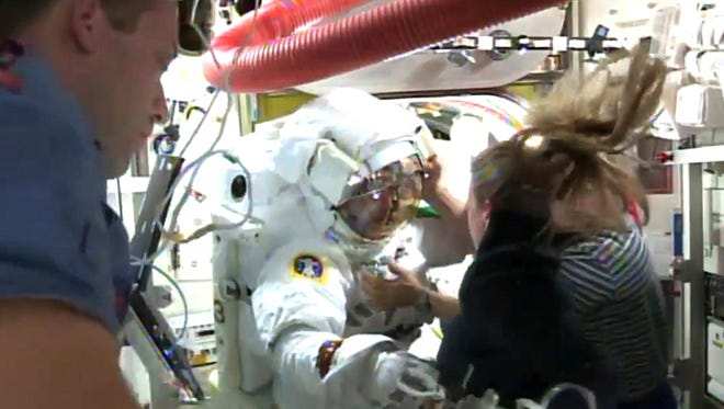 In this July 16, 2013, NASA TV image, crew members attempt to remove the helmet of Luca Parmitano, center, an Italian astronaut stationed on the International Space Station, after it filled with water during a spacewalk.