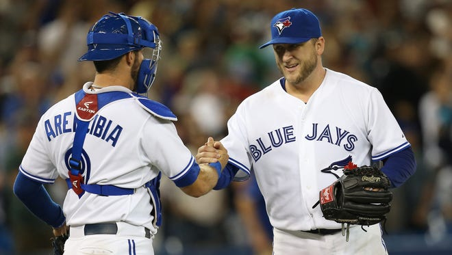 Toronto Blue Jays starting pitcher Mark Buehrle celebrates his complete-game victory with catcher J.P. Arencibia against the Houston Astros at Rogers Centre.