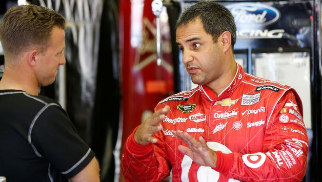 Juan Pablo Montoya talks with A.J. Allmendinger  during practice for the Camping World RV Sales 301 at New Hampshire Motor Speedway.