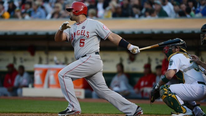 Los Angeles Angels designated hitter Albert Pujols hits an RBI-single during the third inning at O.co Coliseum.