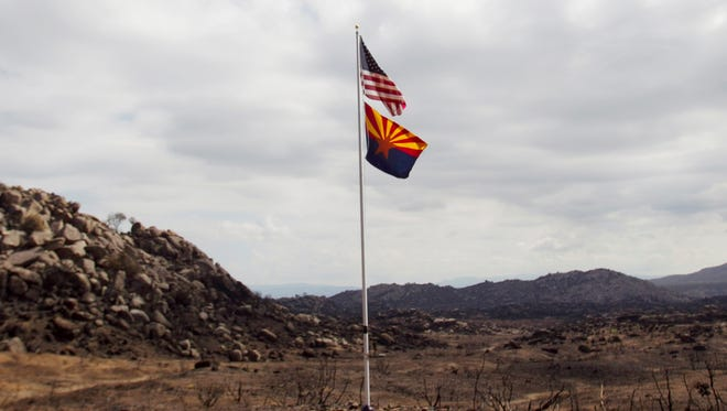 An American flag and Arizona flag flap in the wind on a flagpole seen on Tuesday, July 23, 2013, near the site where 19 firefighters died fighting the Yarnell Hill Fire on June 30, 2013.
