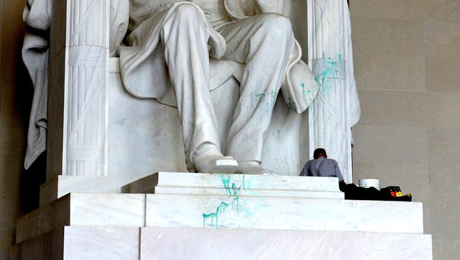 A U.S. Park Service worker removes paint from the Lincoln Memorial Friday morning after vandals splashed the statue at the memorial in Washington.