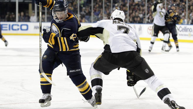 Buffalo Sabres left wing Nathan Gerbe tries to go around Pittsburgh Penguins defenseman Paul Martin.