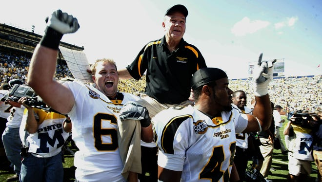 Appalachian State head coach Jerry Moore is lifted on the shoulder of his players moments after their 34-32 upset win over Michigan in 2007.