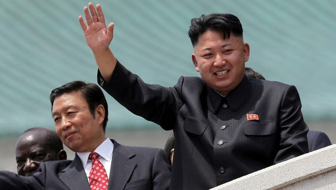 North Korea's leader Kim Jong Un, right, is accompanied by Chinese Vice President Li Yuanchao, center, and Ugandan Vice-President Edward Kiwanuka Ssekand as they greet spectators Saturday, July 27, 2013 during the mass military parade celebrating the 60th anniversary of the Korean War armistice in Pyongyang, North Korea. (AP Photo/Wong Maye-E) ORG XMIT: XWM201