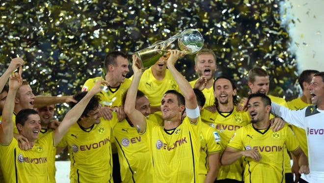Dortmund's midfielder Sebastian Kehl lifts up the trophy after winning the German Super Cup.